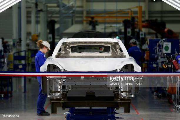 Employees are at work on a production line in a plant of Renault carmaker's subsidiary Alpine on December 14 2017 in Dieppe northwestern France / AFP...
