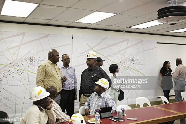 Employees are gathered at the Gold Mine in Doornkop west of Johannesburg on February 5 where a mining accident happened yesterday evening leaving...