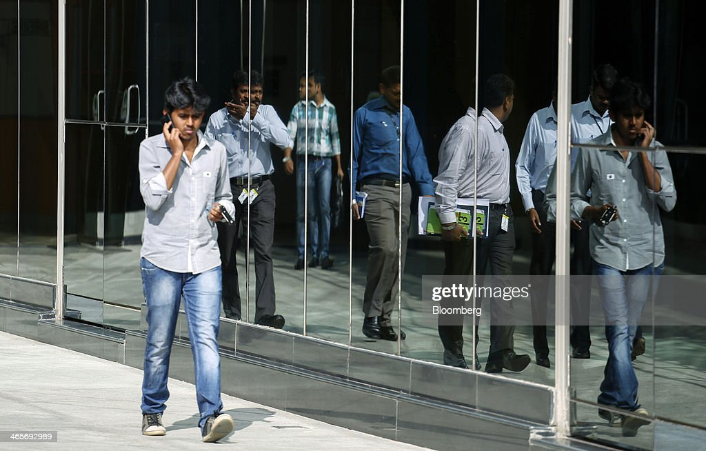 Employees are reflected in the glass facade of a building in the Wipro Ltd. campus in Bangalore, India, on Tuesday, Jan. 28, 2014. Worldwide spending on information technology will grow 3.1 percent to $3.8 trillion this year, with IT services set to climb 4.5 percent, researcher Gartner Inc. forecast Jan. 6. Photographer: Vivek Prakash/Bloomberg via Getty Images