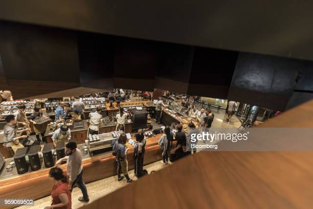 Employees are seen from an upper floor as they work behind a counter inside the Starbucks Corp Reserve Roastery store in Shanghai China on Friday May...