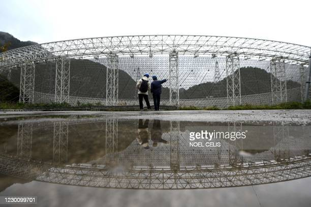 Employees are seen in front of the Five-hundred-meter Aperture Spherical radio Telescope at the National Astronomical Observatories, Chinese...
