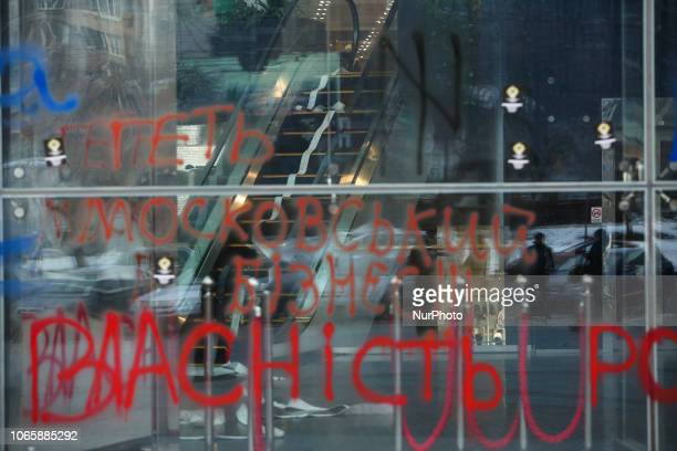 Employees are seen through the shop window of Ocean Plaza Mall painted by rallying nationalists with slogans quotGet Russian business outquot and...