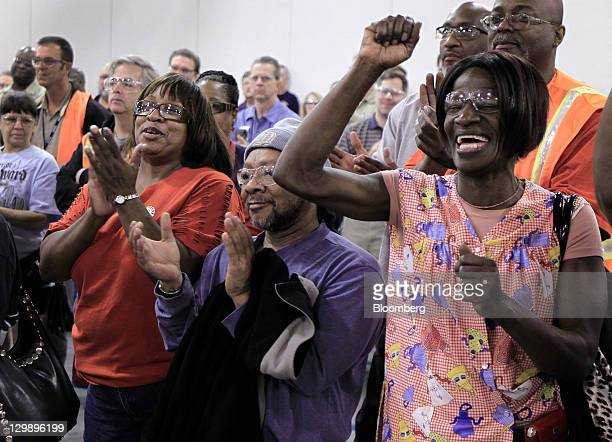 Employees Aretha Lee from left Dennie Grant and Debra Wilson cheer during an event at the General Motors Co transmission plant in Warren Michigan US...