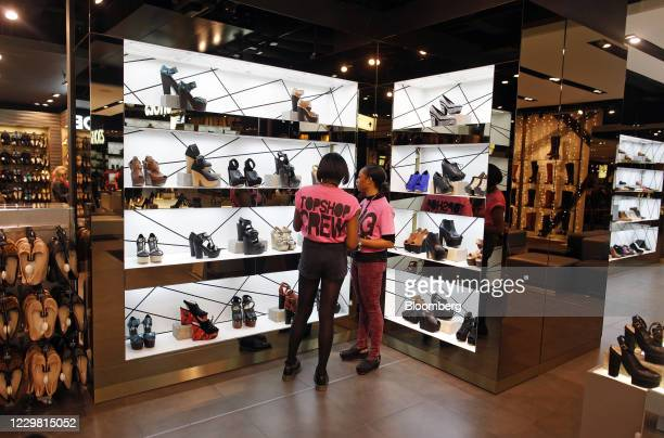 Employees arrange a display of women's footwear in the shoe department of a Topshop store, owned by Arcadia Group Ltd., on Oxford Street in London,...