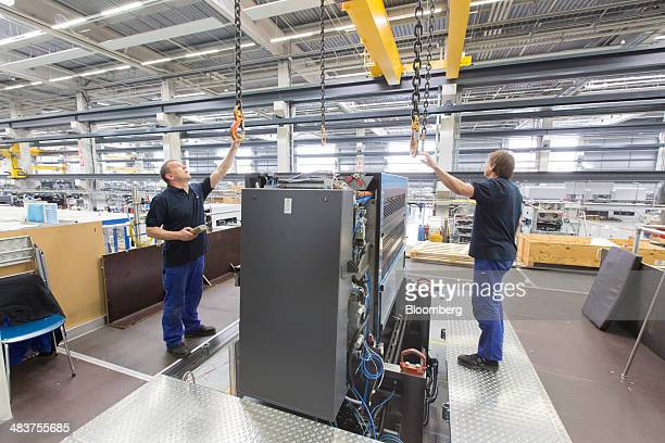Employees arrange lifting hooks on a winch as they prepare to lift a section of a Heidelberg industrial printing press in the Heidelberger...