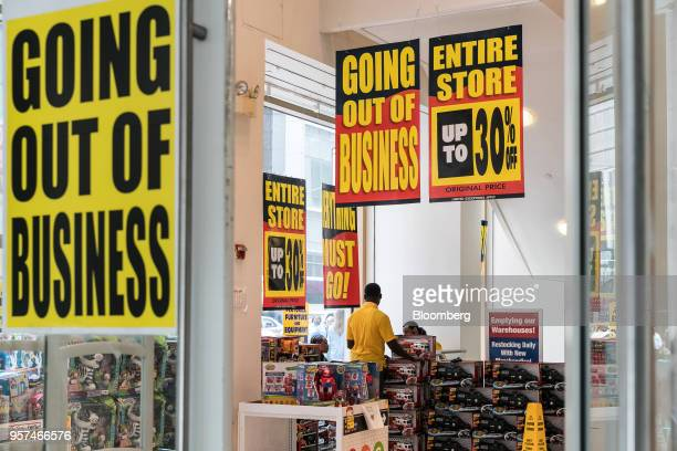 Employees arrange merchandise under a Going Out Of Business sign at a Toys 'R' Us retail store at Times Square in New York US on Friday May 11 2018...