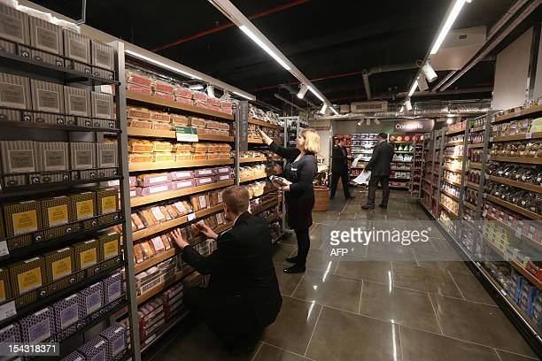Employees arrange products on shelves prior to the inauguration of a new Marks Spencer on October 18 2012 at the So Ouest shopping center in...