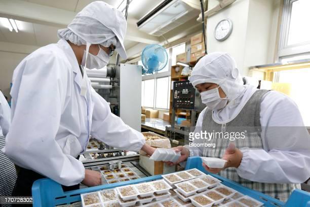 Employees arrange sachets of seasoning sauce and mustard onto polystyrene trays of fermented soybeans known as natto at the Matsushita Shoten YK...