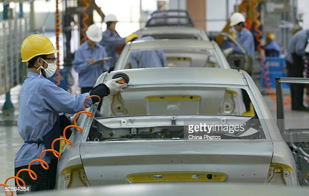 Employees assemble a cars in Mazda's Family line of vehicles at China First Automobile Works Group Haima Automobile Co Ltd April 6 2005 in Haikou...