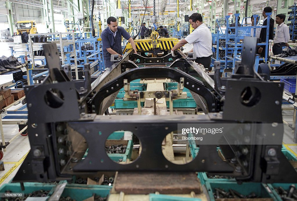 Employees assemble a chassis on the assembly line for the Mahindra & Mahindra Ltd. Navistar truck at the company's factory in Chakan, Maharashtra, India, on Wednesday, Feb. 6, 2013. Mahindra & Mahindra is scheduled to announce third-quarter earnings today. Photographer: Kuni Takahashi/Bloomberg via Getty Images