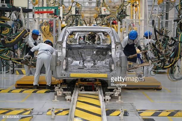 Employees assemble a Mitsubishi Motors Corp sports utility vehicle on a production line at the company's plant in Cikarang Indonesia on Tuesday April...