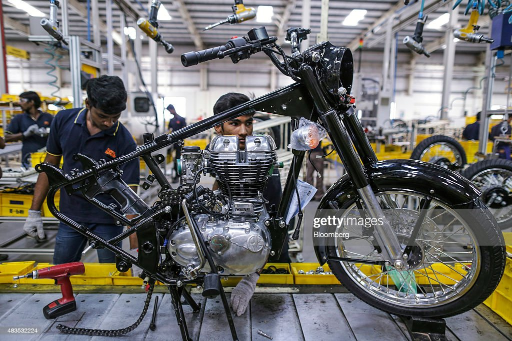 Employees assemble a Royal Enfield Motors Ltd Classic 350 motorcycle moving on a conveyor on the production line at the company`s manufacturing...