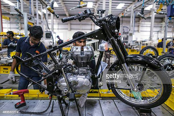 Employees assemble a Royal Enfield Motors Ltd Classic 350 motorcycle moving on a conveyor on the production line at the company's manufacturing...