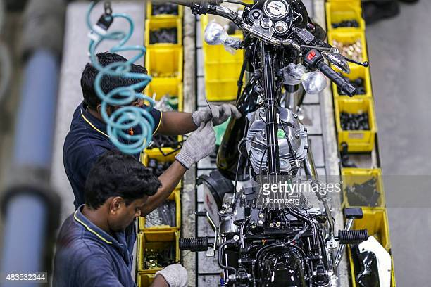 Employees assemble a Royal Enfield Motors Ltd. Classic 350 motorcycle moving on a conveyor on the production line at the company's manufacturing...