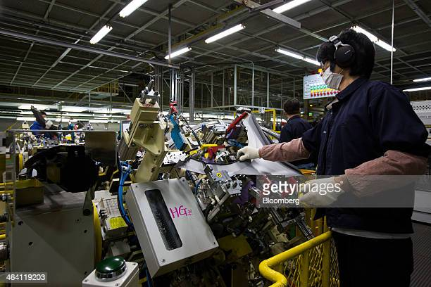 Employees assemble Hyundai Motor Co. Vehicles on the production line at the company's factory in Asan, South Korea, on Monday, Jan. 20, 2014....