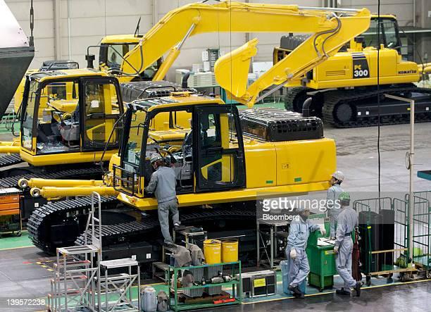Employees assemble Komatsu Ltd excavators on the production line of the company's plant in Hirakata City Osaka Japan on Thursday Feb 23 2012 Komatsu...