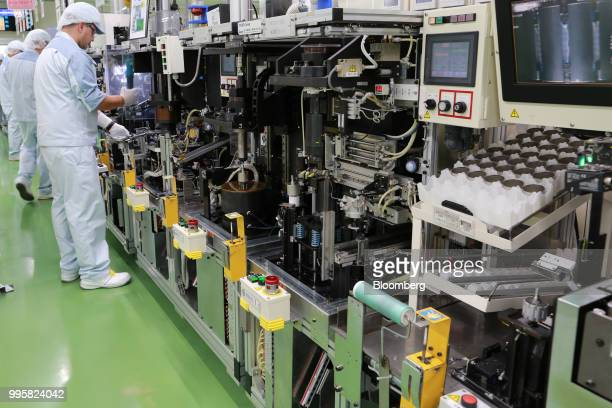 Employees assemble motor control units on the production line of Jtekt Corp's Hanazono plant in Okazaki Aichi Prefecture Japan on Tuesday July 10...
