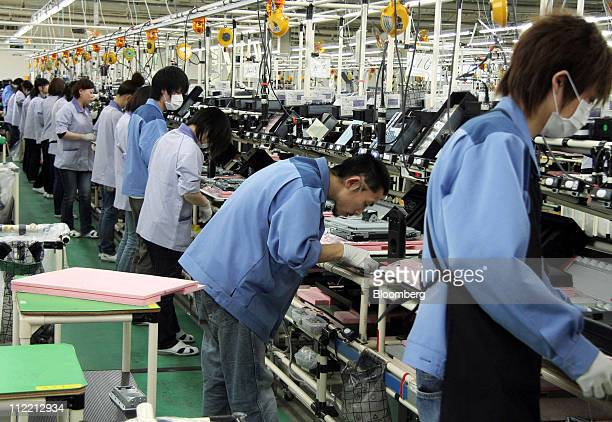 Employees assemble parts for Fujitsu Ltd computers on the production line of the Fujitsu Isotec Ltd plant in Date city Fukushima prefecture Japan on...