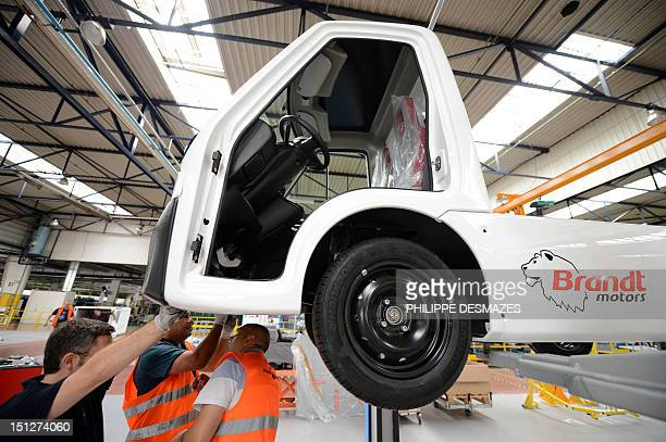 Employees assemble parts of a Citelec electric or hybrid utility vehicle on September 5 2012 at FagorBrandt factory in Lyon centraleastern France...