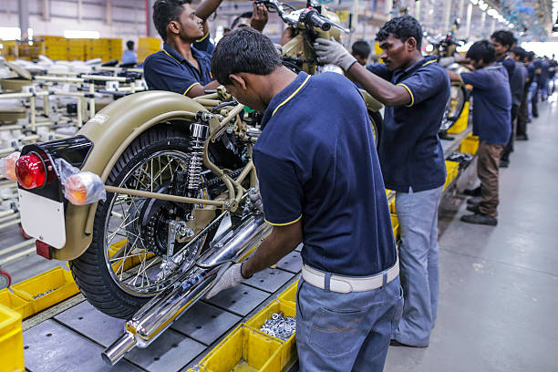 Employees assemble Royal Enfield Motors Ltd Classic 350 motorcycles moving on a conveyor on the production line at the company`s manufacturing...