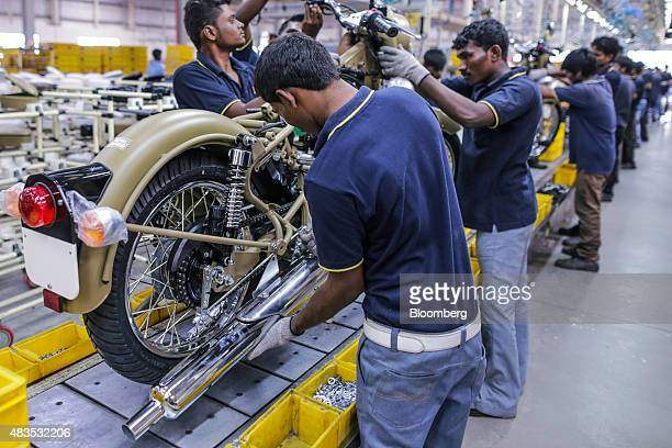 Employees assemble Royal Enfield Motors Ltd. Classic 350 motorcycles moving on a conveyor on the production line at the company's manufacturing...