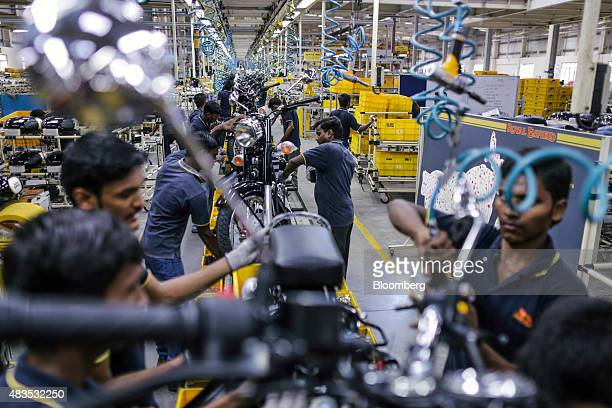 Employees assemble Royal Enfield Motors Ltd Classic 350 motorcycles moving on a conveyor on the production line at the company's manufacturing...