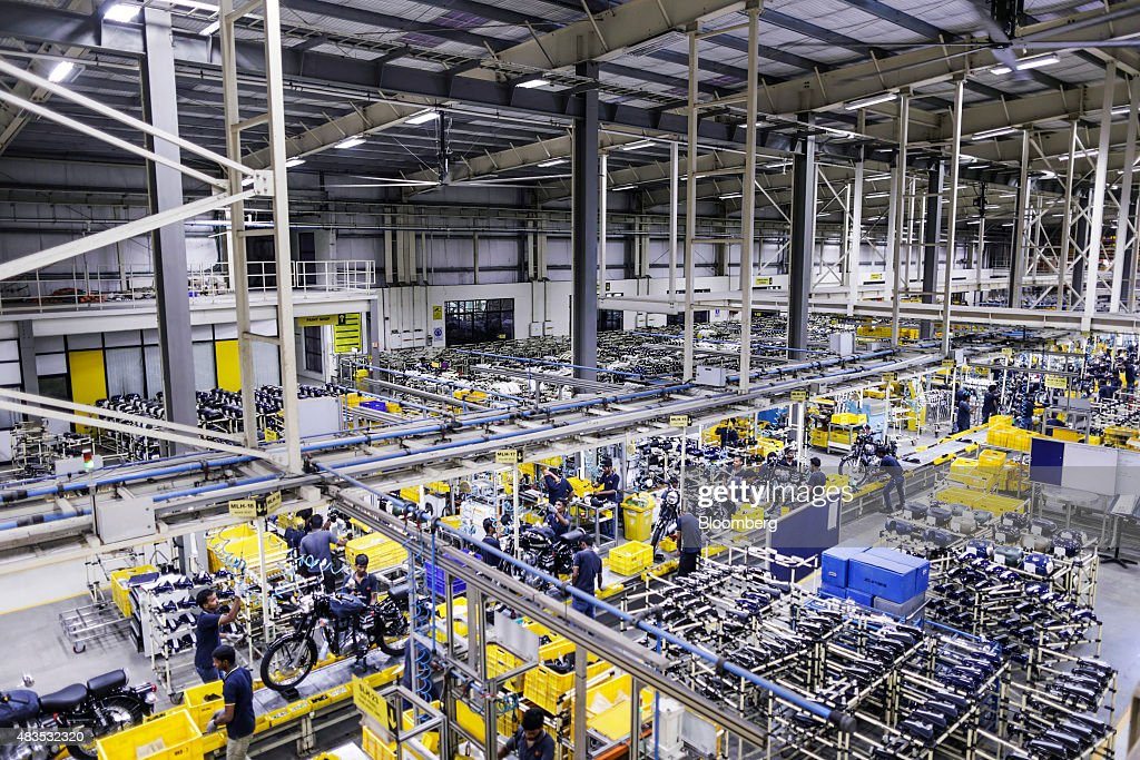 Employees assemble Royal Enfield Motors Ltd motorcycles moving on a conveyor on the production line at the company`s manufacturing facility in...