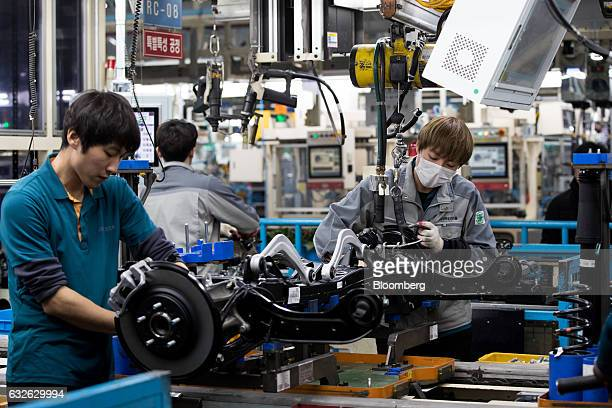 Employees assemble vehicle chassis modules on a production line at the Hyundai Mobis Co factory in Asan South Chungcheong South Korea on Tuesday Jan...