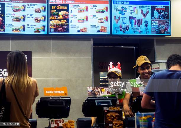 Employees assist customers at a Burger King do Brasil restaurant in Sao Paulo, Brazil, on Monday, Dec. 11, 2017. Burger King do Brasil may raise as...