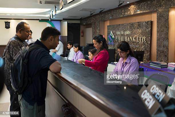 Employees assist customers at a service counter inside a Civil Bank Ltd branch in Kathmandu Nepal on Thursday May 28 2015 Nepal's gross domestic...