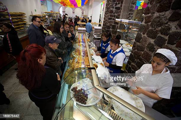 Employees assist customers at La Ideal bakery in Mexico City Mexico on Thursday Oct 24 2013 The pan de muerto or bread of the dead is a sweet soft...