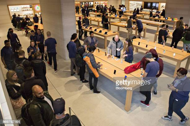 Employees assist customers with Apple Inc iPhone X smartphones during the sales launch at a store in Chicago Illinois US on Friday Nov 3 2017 The...
