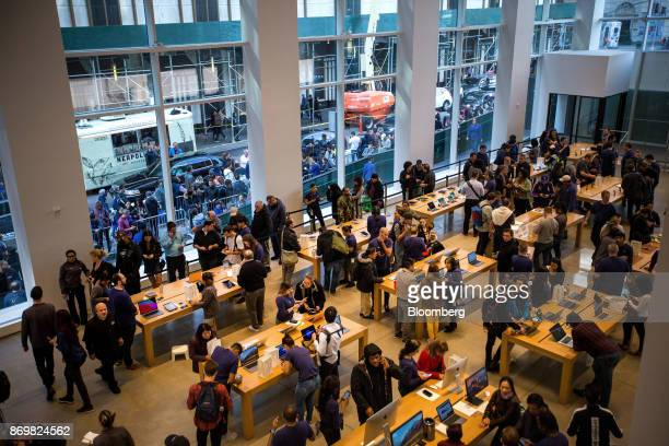 Employees assist customers with Apple Inc iPhone X smartphones during the sales launch at a store in New York US on Friday Nov 3 2017 The $1000 price...