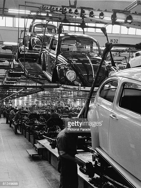 Employees at a Volkswagen plant work on an assembly line to complete Volkswagen 1200 Sedans better known as Beetles Wolfsburg Germany 1960s In the...