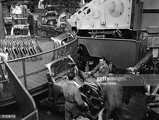 Employees at a Volkswagen plant work on an assembly line to complete Volkswagen 1200 Sedans better known as Beetles Wolfsburg Germany 1960s They...