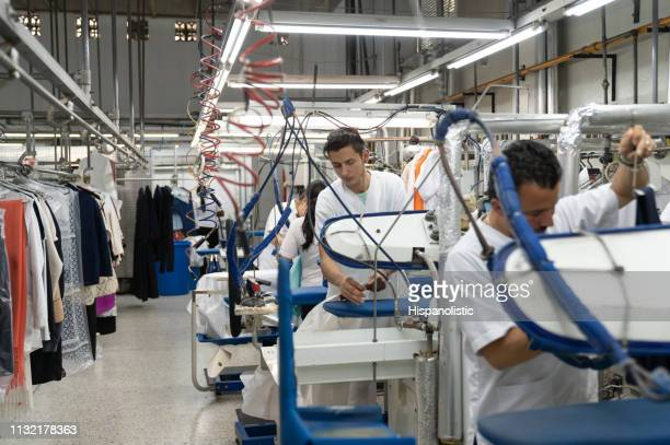 employees at an industrial laundry service ironing clothes - dry cleaned stock pictures, royalty-free photos & images
