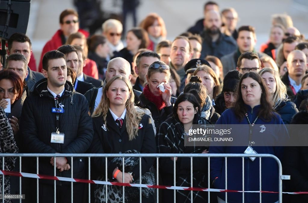 TOPSHOT - Employees at Brussels' international airport in Zaventem gather for a memorial ceremony to mark the first anniversary of the twin Brussels attacks by Islamic extremists on March 22, 2017. Belgium marks the first anniversary of the Islamic State bombings in Brussels, one at the airport and the other in the metro, in which 32 people were killed and more than 320 wounded with ceremonies showing that the heart of Europe stands defiant. / AFP PHOTO / BELGA AND AFP PHOTO / Emmanuel DUNAND