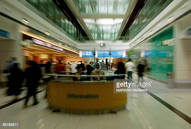 Employees at Dubai International Airport's new Terminal 3 sit behind an information desk at the duty free market on October 9 2008 The fast growing...