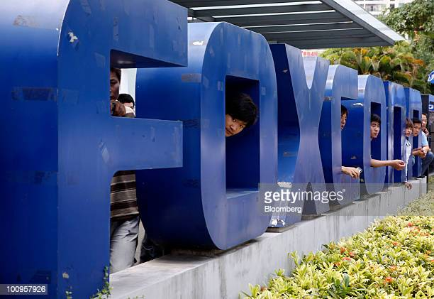 Employees at Hon Hai's Foxconn plant peek out from the back of a company sign in Shenzhen China on Wednesday May 26 2010 Apple Inc HewlettPackard Co...