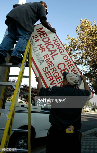 –Employees at Martin Luther King Jr Harbor Hospital remove the emergency entrance signs in front of the hospital after the medical center failed its...