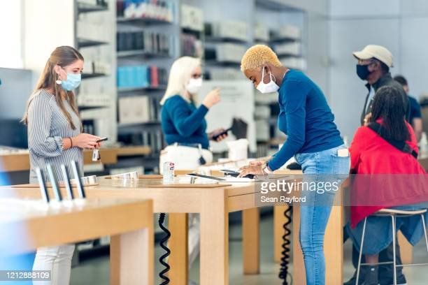 Employees at the Apple Store help customers on May 13, 2020 in Charleston, South Carolina. Customers had temperatures taken and were required to wear...