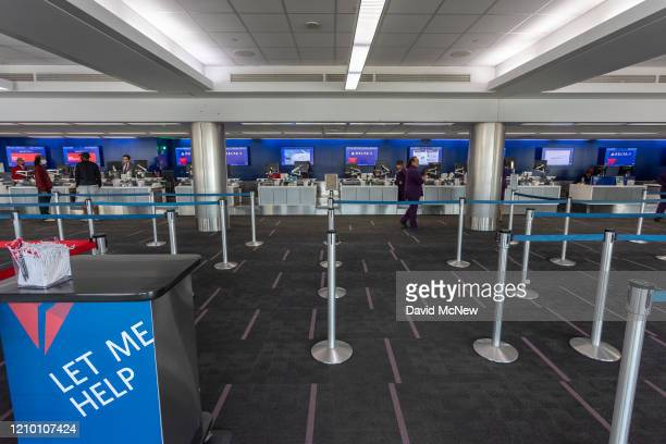 Employees at the Delta Air Lines counters wait for customers at a nearly deserted Los Angeles International Airport due to the coronavirus pandemic...