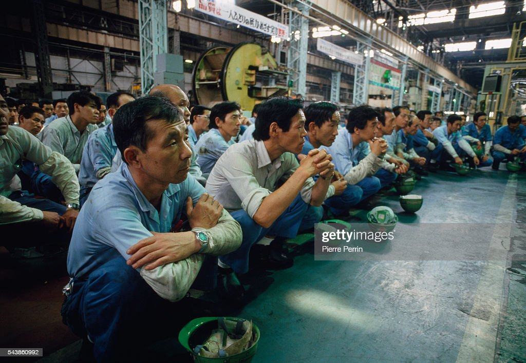 Employees Attend A Meeting On The Production Line Shop Floor At