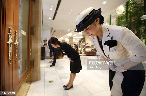 Employees bow to welcome customers ahead of the day's opening at an entrance to the Mitsukoshi department store operated by Isetan Mitsukoshi...