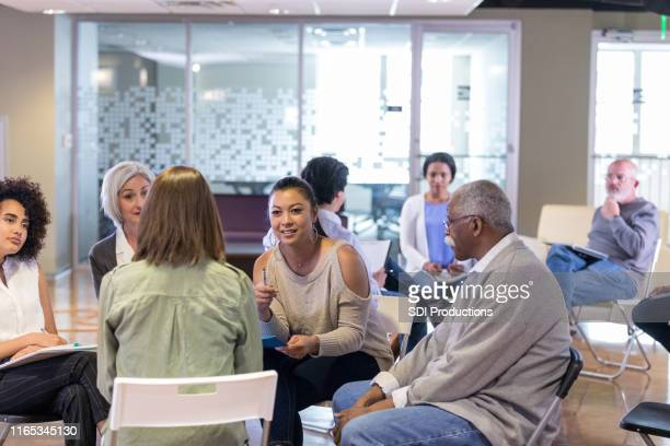 employees brainstorm ideas during weekly meeting - community meeting stock pictures, royalty-free photos & images