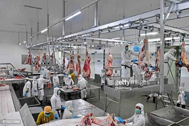 Employees butcher trim and sort buffalo meat in the sorting area of an abbatoir operated by Allana Group in Aligarh Uttar Pradesh India on Tuesday...
