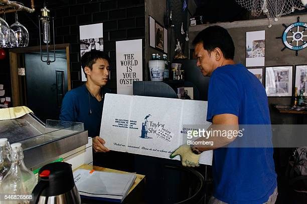 Employees carry a box of seafood into a Taylor Shellfish Farms restaurant in the Sai Ying Pun area of Hong Kong China on Friday June 17 2016 Geoducks...