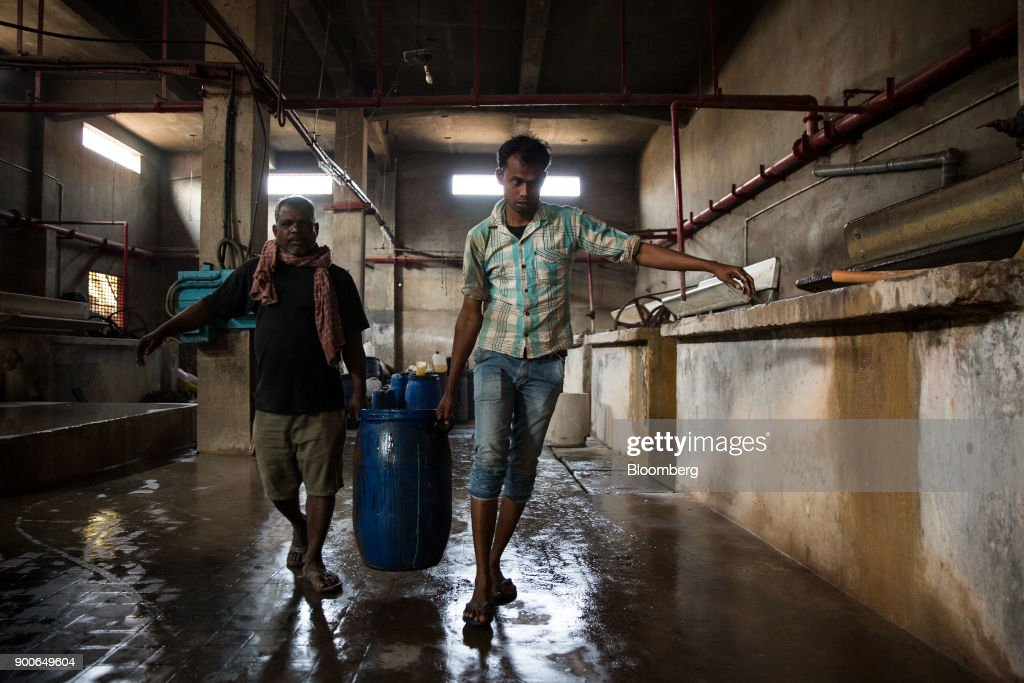 Employees carry a container of chemicals at the Sheong Shi Tannery in Kolkata, West Bengal, India on Tuesday, Dec. 26, 2017. India's manufacturing sector grew in December as the Nikkei India Manufacturing Purchasing Managers' Index (PMI) rose to 54.7 from 52.6 in November, with a number above 50 indicating expansion. Photographer: Taylor Weidman/Bloomberg via Getty Images