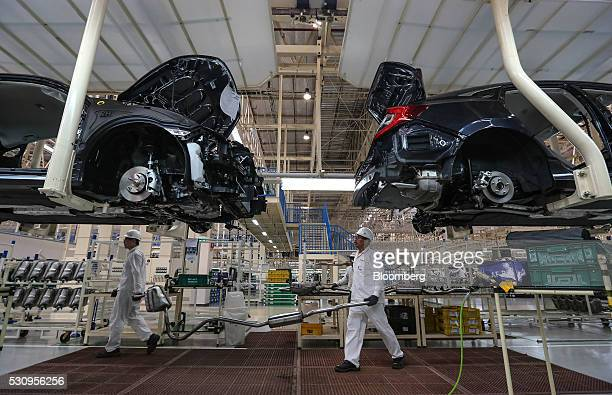 Employees carry an exhaust pipe as they work on the production line of the Honda Motor Co assembly plant in Prachinburi Thailand on Thursday May 12...