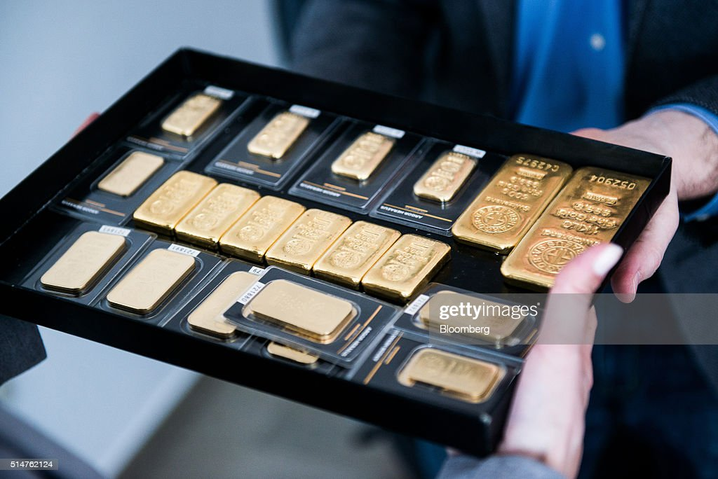Employees carry mixed rate weighted gold bars in a storage tray in this arranged photograph at Solar Capital Gold Zrt. in Budapest, Hungary, on Thursday, March 10, 2016. Gold advanced to the highest level in a year after the European Central Bank indicated it wouldn't cut interest rates further, boosting the euro and making dollar-denominated bullion less expensive for investors. Photographer: Akos Stiller/Bloomberg via Getty Images